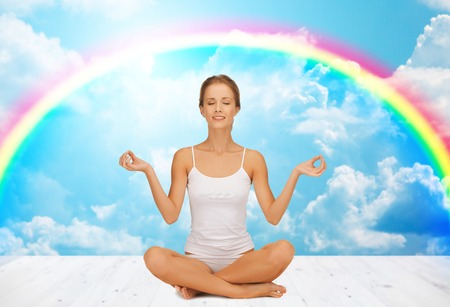 pranayama: people, health, wellness and meditation concept - woman in underwear meditating in yoga lotus pose on wooden floor over white clouds and rainbow on blue sky background Stock Photo
