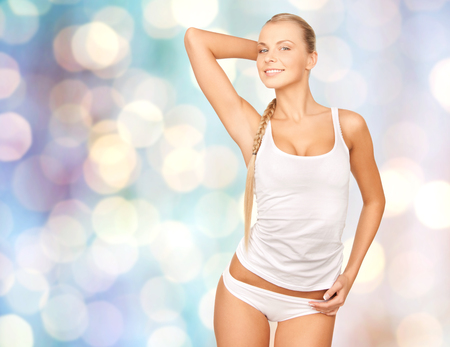 beautiful body: people, beauty, body care and fashion concept - happy beautiful young woman in cotton underwear posing over blue holidays lights background