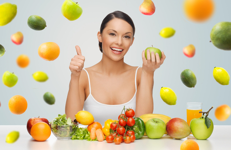 people, diet, gesture and vegetarian concept- happy asian woman with healthy food showing thumbs up over gray background with falling fruits