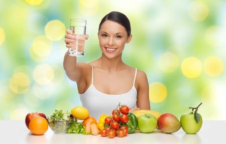 agua potable: Personas, la dieta vegetariana y el concepto - mujer asiática feliz con el alimento sano que muestra vaso de agua sobre fondo verde luces Foto de archivo