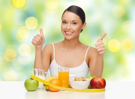 dieta saludable: la gente, el gesto y la dieta concepto-mujer asiática feliz con los pulgares de alimentos saludables que muestra las luces de arriba sobre el fondo verde