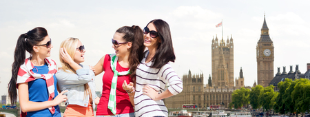 kingdom: summer, holidays, vacation, friendship and people concept - happy teenage girls or young women in sunglasses talking and laughing over houses of parliament in london background Stock Photo