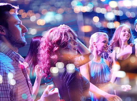 dancing club: party, holidays, celebration, nightlife and people concept - smiling friends dancing in club