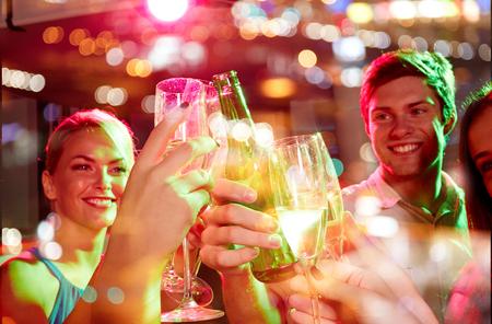 gente celebrando: fiesta, d�as de fiesta, celebraci�n, vida nocturna y la gente concepto - sonriendo amigos que tintinean los vidrios de champ�n y la cerveza en el club