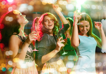 sparkling wine: party, holidays, celebration, nightlife and people concept - smiling friends with glasses of champagne dancing in club