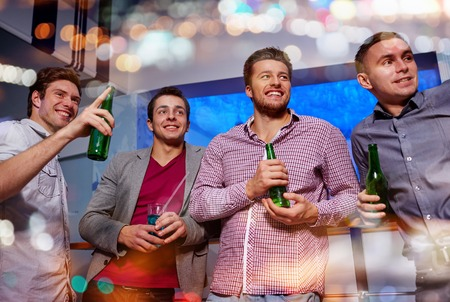 vida nocturna, fiesta, la amistad, el ocio y el concepto de personas - grupo de amigos sonrientes masculinas con las botellas de cerveza que bebe y que señala el dedo a algo en el club nocturno