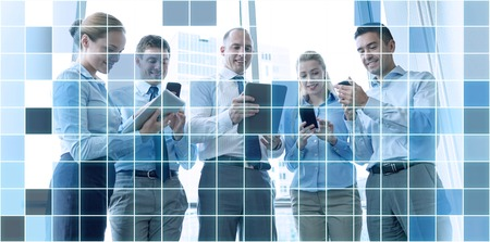 business, teamwork, people and technology concept - business team with tablet pc and smartphones meeting in office over blue squared grid background