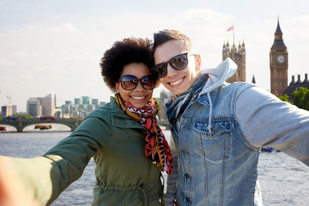 black couple: tourism, travel, people, leisure and technology concept - happy teenage international couple taking selfie over houses of parliament and thames river in london background Stock Photo