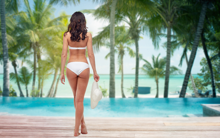 people, travel, swimwear, summer and beauty concept - young woman in white bikini swimsuit from back over tropical beach with palm trees and pool at hotel resort background