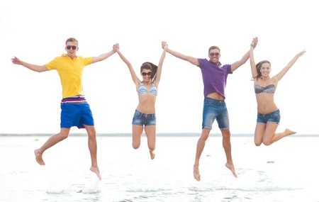 people having fun: summer holidays, vacation, tourism, travel and people concept - group of happy friends holding hands and jumping on beach