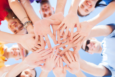 many hands: togetherness, team, union, people and gesture concept - close up of many hands over blue sky background