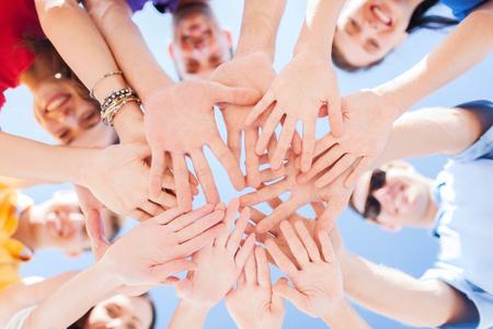 mucha gente: Unión, equipo, unión, la gente y el gesto concepto - cerca de muchas manos sobre fondo de cielo azul Foto de archivo