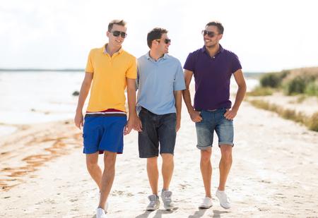 友情、夏休み、休日、人々 コンセプト - ビーチに沿って歩いてサングラスの男性友達に笑顔のグループ 写真素材