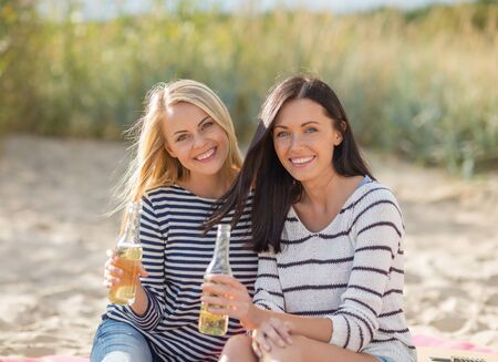 nonalcoholic beer: summer holidays, vacation, celebration and people concept - happy teenage girls or young women drinking beer or lemonade on beach