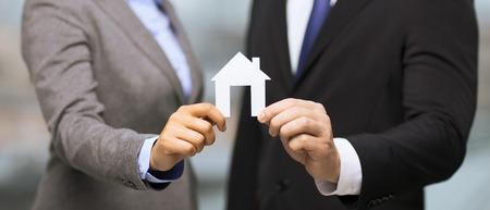 Business, eco, immobilier et concept de bureau - homme d'affaires et femme d'affaires tenant maison de papier blanc dans le bureau
