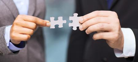 zakelijke en office concept - zakenman en zakenvrouw probeert te passen puzzel stukjes in het kantoor te sluiten