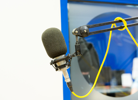 commentator: technology, electronics and audio equipment concept - close up of microphone at recording studio or radio station