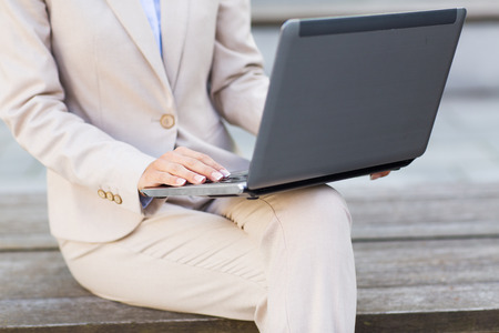 woman business suit: business, technology and people concept - close up of smiling woman with laptop computer sitting on bench in city Stock Photo