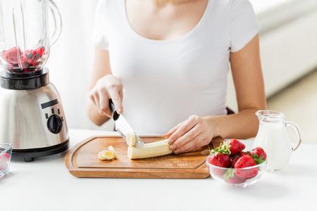 tomando leche: alimentación saludable, cocinar, comida vegetariana, la dieta y el concepto de la gente - cerca de la mujer joven con la batidora de plátano cortar las sacudidas de la fruta en el país