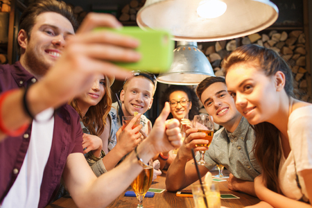 pubs: people, leisure, friendship, technology and communication concept - group of happy smiling friends with smartphone and drinks taking selfie at bar or pub