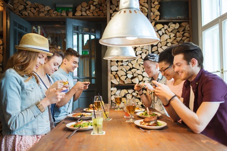 people, leisure, friendship, technology and internet addiction concept - group of happy smiling friends with smartphones taking picture of food at bar or pub. Stock Photo