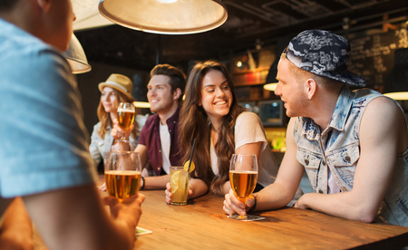 beer in bar: people, leisure, friendship and communication concept - group of happy smiling friends drinking beer and cocktails talking at bar or pub