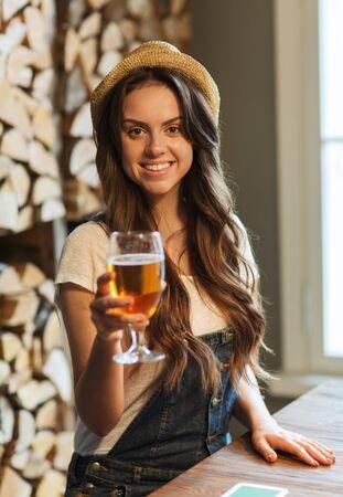 tomando alcohol: la gente, las bebidas, el alcohol y el concepto de ocio - agua potable de mujer joven pelirroja feliz en el bar o pub