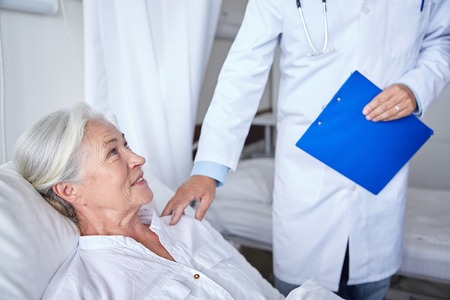 health care and medicine: medicine, age, health care and people concept - doctor visiting happy senior woman at hospital Stock Photo