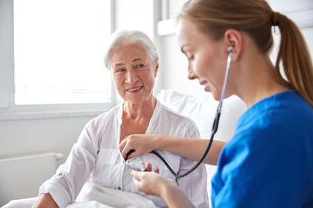 stethoscope: medicine, age, support, health care and people concept - doctor or nurse with stethoscope visiting senior woman and checking her heartbeat at hospital ward
