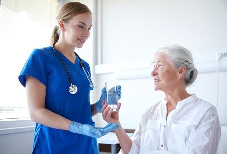 Medizin, Alter, Gesundheitswesen und Menschen Konzept - Krankenschwester Medikamente und ein Glas Wasser auf ältere Frau am Krankenstation geben