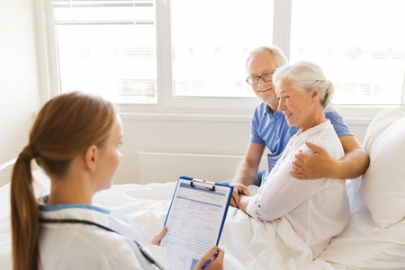 man doctor: medicine, age, health care and people concept - senior woman, man and doctor with clipboard at hospital ward Stock Photo