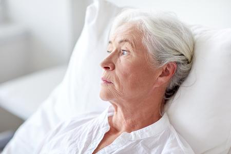 la medicina, la edad, la salud y las personas concepto - mujer mayor paciente acostado en la cama en la sala del hospital Foto de archivo
