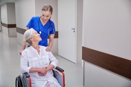 vecchiaia: la medicina, l'età, il supporto, l'assistenza sanitaria e la gente concetto - infermiera felice prendendo donna paziente anziano in sedia a rotelle a corridoio dell'ospedale Archivio Fotografico
