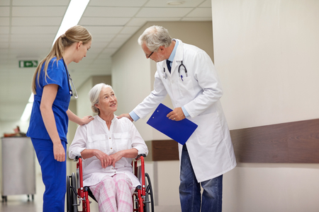 nursing aid: medicine, age, health care and people concept - doctor, nurse and senior woman patient in wheelchair at hospital corridor