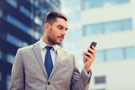 mobile app: business, technology and people concept - serious businessman with smartphone over office building Stock Photo