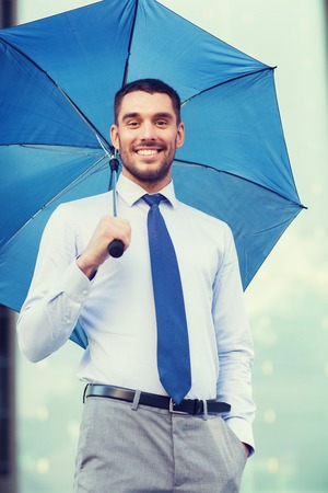 uomo sotto la pioggia: business, bad weather and people and concept - young smiling businessman with umbrella outdoors