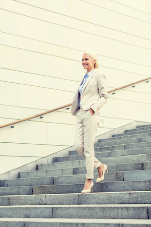 bajando escaleras: business, people and education concept - young smiling businesswoman walking down stairs outdoors Foto de archivo