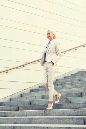 down stairs: negocio, la gente y el concepto de la educación - joven empresaria sonriente caminando por las escaleras al aire libre Foto de archivo