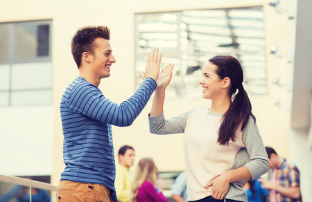 high school girl: friendship, gesture, education and people concept - group of smiling students outdoors making high five