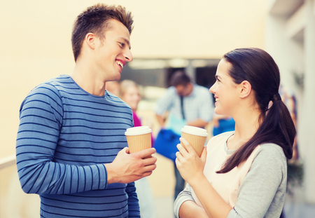 teen couple: friendship, people, drinks and education concept - group of smiling students with paper coffee cups outdoors