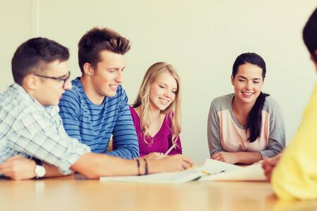 education, school, architecture and people concept - group of smiling students with blueprint meeting indoors Stock Photo