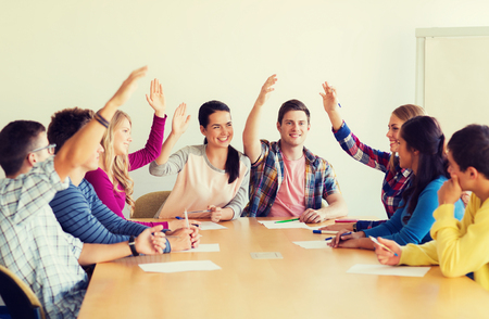 voting: education, teamwork and people concept - group of smiling students with papers raising hands and voting indoors