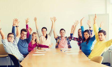 manos juntas: la educación, el trabajo en equipo y el concepto de la gente - grupo de estudiantes sonrientes que levantan las manos en la oficina Foto de archivo