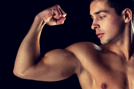 sport, bodybuilding, strength and people concept - close up of young man showing biceps over black background Stock Photo
