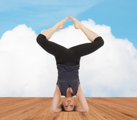 counterbalance: sport, fitness, yoga, people and health concept - happy young woman doing headstand exercise on wooden berth over white cloud and blue sky background