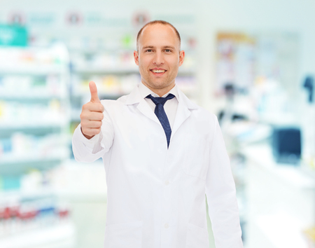 white coat: medicine, pharmacy, people, health care and pharmacology concept - smiling male pharmacist in white coat showing thumbs up over drugstore background