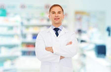 coat of arms: medicina, farmacia, la gente, la atención médica y el concepto de la farmacología - sonriendo farmacéutico de sexo masculino en la capa blanca sobre fondo droguería