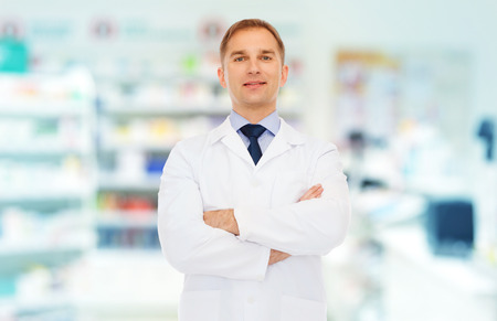 coat: medicine, pharmacy, people, health care and pharmacology concept - smiling male pharmacist in white coat over drugstore background