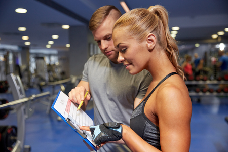 weight loss plan: fitness, sport, exercising and diet concept - smiling young woman with personal trainer and exercise plan on clipboard in gym