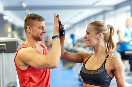 personal trainer: sport, fitness, lifestyle, gesture and people concept - smiling man and woman doing high five in gym